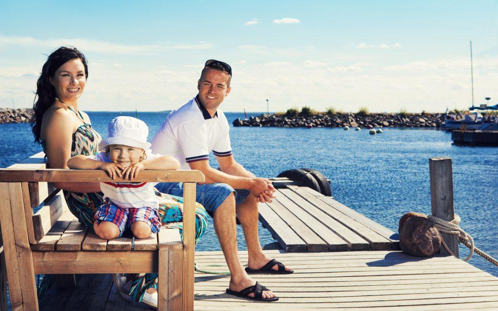 Äiti, isä ja poika auringon paisteessa istumassa merellisen maiseman ääressä puulaiturilla..
