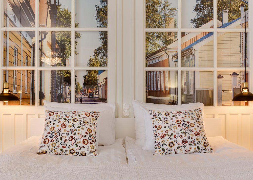 Original Sokos Hotel Kaarlen kahden hengen huoneen parivuode, jonka taustalla sängyn päätynä valkoiset ikkunakehykset joiden takana näkyy vsuuri valokuva suurennos vanhakaupunki Neristanista