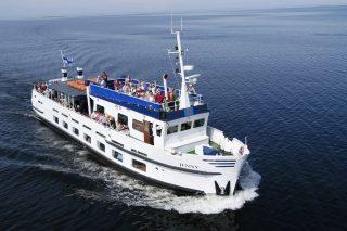 177 paikkainen ms Jenny purjehtii aurinkoisessa ja tyynessä kelissä kohti Tankarin majakkasaarta ihmisiä aurinkokannella