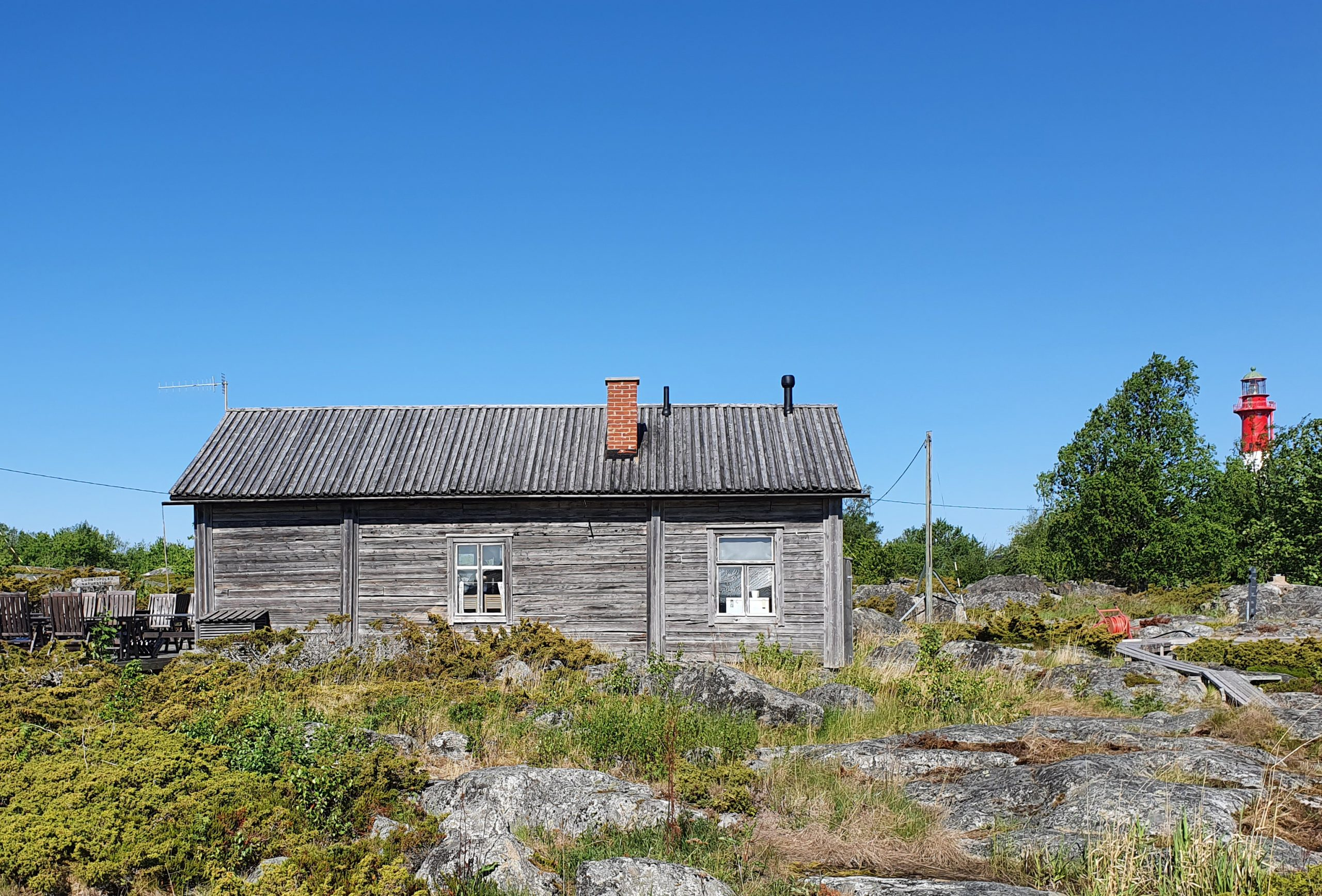 Tankarin majakkasaarella toimiva Café Tankarin rakennus, joka on kauniisti patinoitunut saaren vehreään mutta kalliomaiseen ympäristöön.