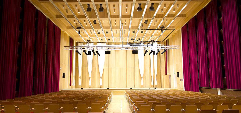 Snellman-salin juhlatila tuoleillakalustettuna, jossa molemmilla renunoilla viininpunaiset verhot latiasta kattoon, etualalla itse esiintymislava valaistuksiineen.