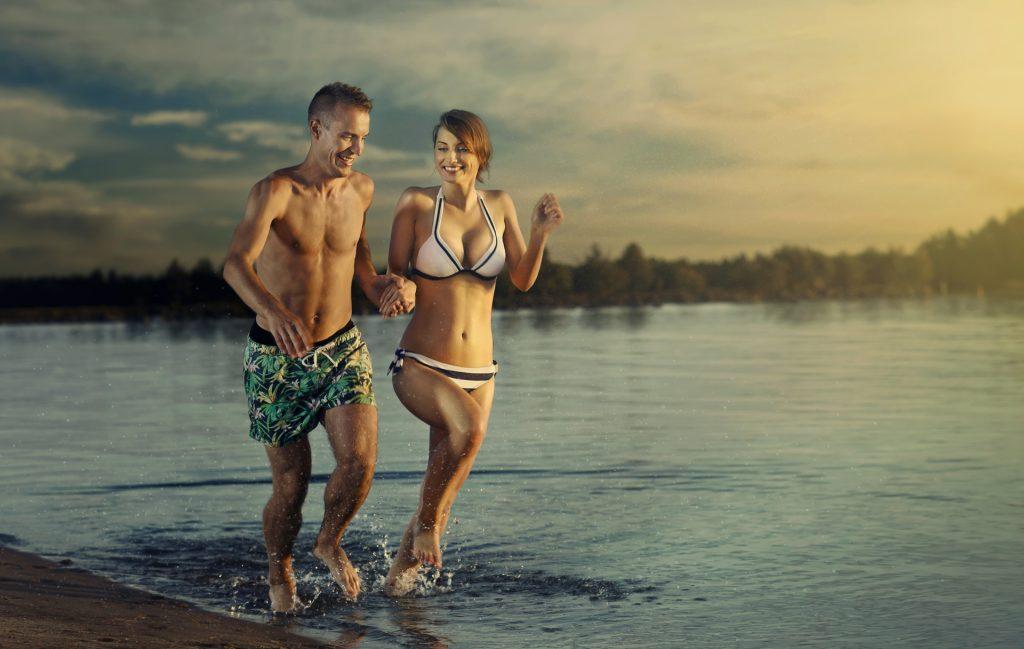 Nuori pari mies ja nainen juoksevat käsikädessä pitkin uimarannan rantaviiva. Vesi on tyyni.