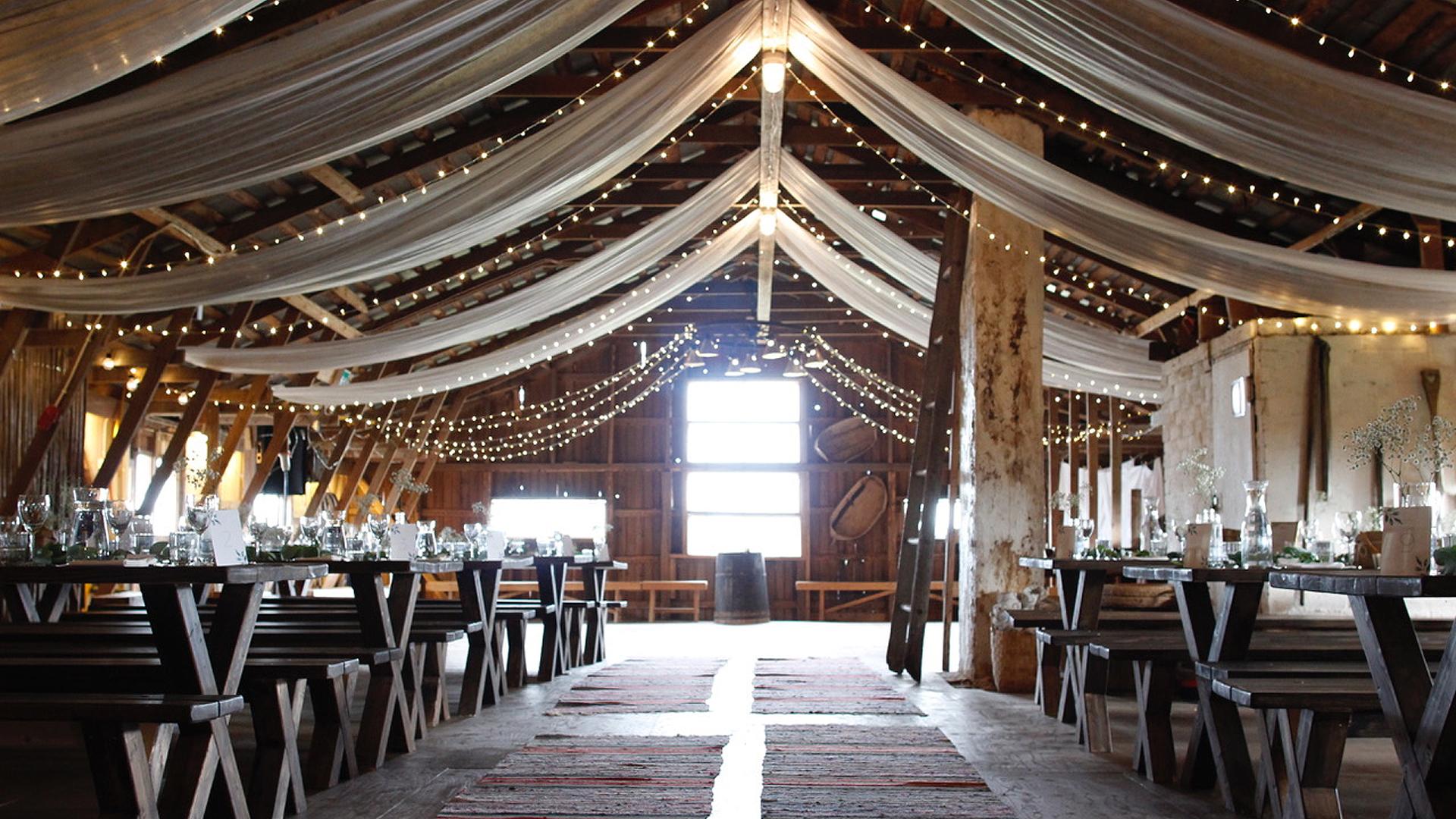 Jukkolan Navetanvintti on tyylikäs nimensä mukainen juhlapaikka, jossa pitkät pitopöydät on järjestelty valkoisten katosta roikkuvien kankaiden alapuolelle. päätyikkuvasta kajastaa auringonvalo joka valaisee tilaa pehmeästi.