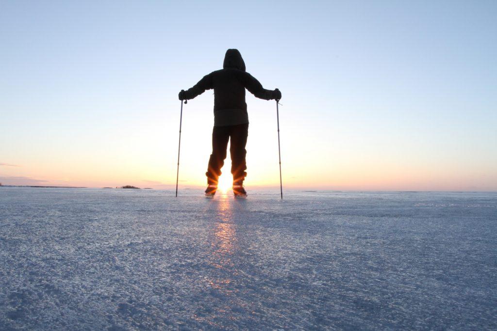 Kokkolassa luonto on lähellä. Talvi on jäädyttänyt meren ja mies on lähtenyt retkiluistelemaan. Aurinko paistaa taivaanrannassa, aivan jään pinnan yläpuolella ja luo viimeisiä valonsäteitään mieheen. Kuvaaja Miia Parviainen.