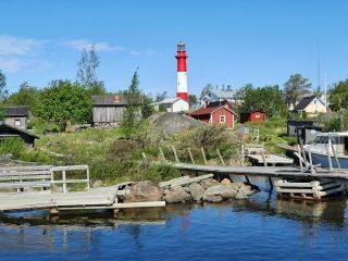Tankarin majakkasaari kauniina kesäpäivänä. Punavalkea majakka hallitsee kokonaisuutta punaisten mökkien lomasta. Rannassa on veneitä.