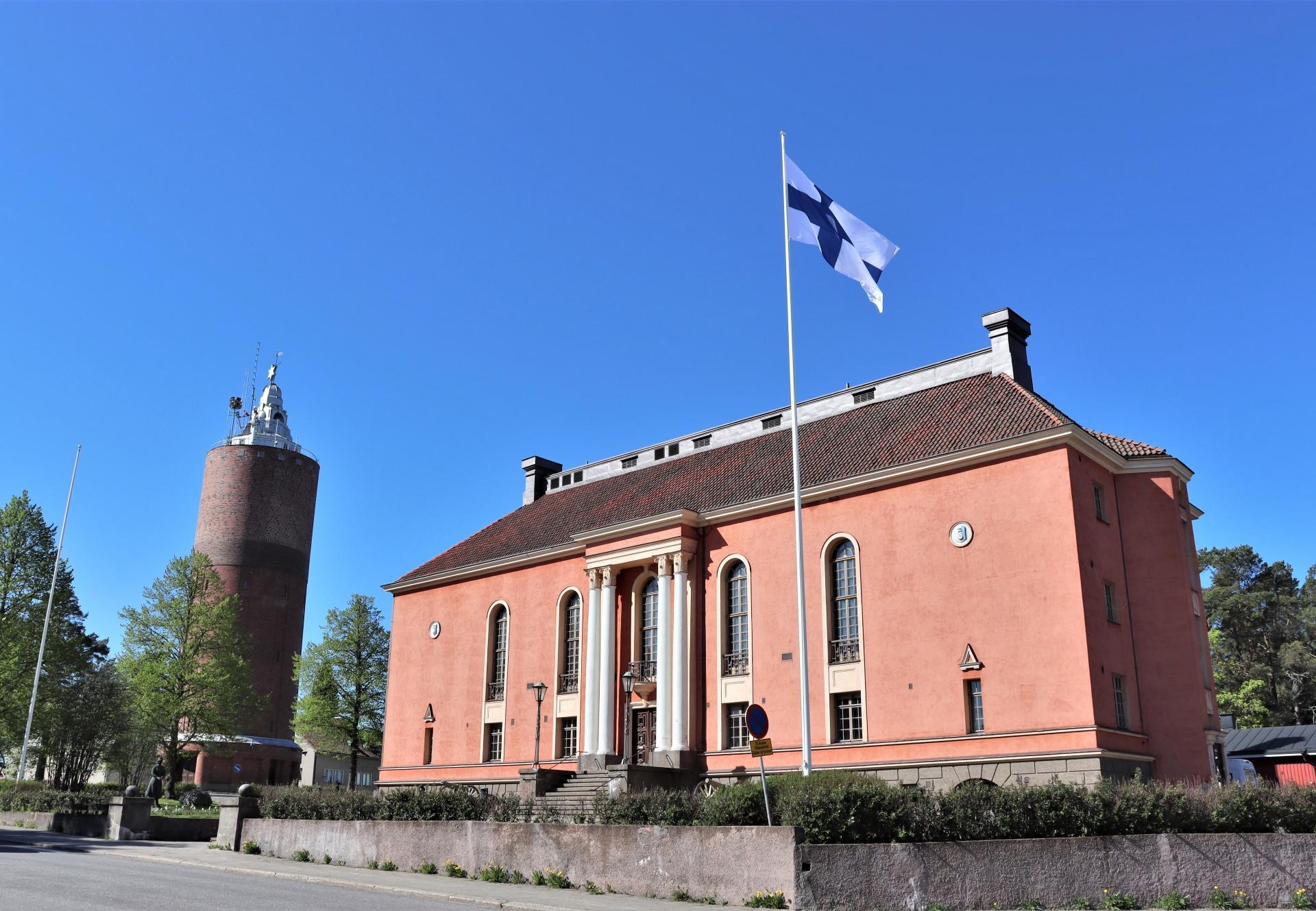 Kokkolan kaupunginteatterin rakennus Vartiolinna on upea näky Pompejin punaisine seinineen ja valkoisine pilareineen. Vartiolinnan vieressä seisoo myös vanha vesitorni. Kesäinen päivä valaisee Vartiolinnaa ja Suomen lippu liehuu salossa.