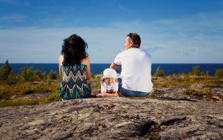 Kokkola on hyvä paikka asua lapsiperheille. Vanhemmat nauttivat aurinkoisesta päivästä katsellen merelle päin kalliiokivetyksellä ja lapsi makoilee heidän välissään iloisena.