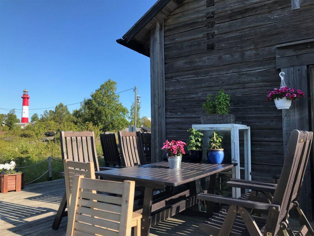 Tankarin kahvilassa voit käydä syömässä maittavan lohikeittoaterian vieraillessasi Tankarissa. Aurinkoisella terassilla on kukkia ja majakka siintää taustalla.