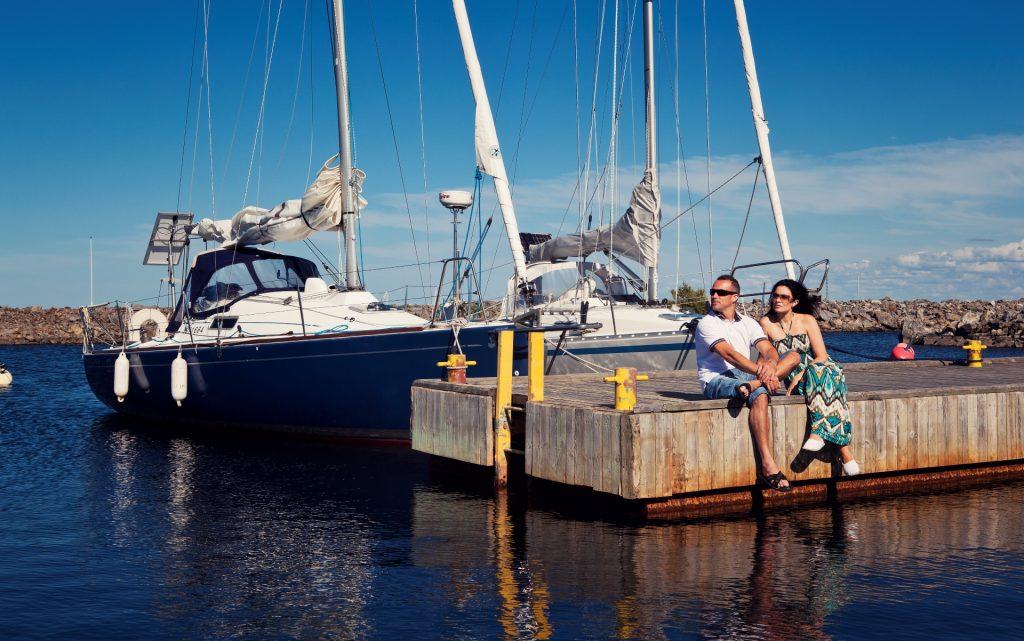 Pariskunta istuu Tankarin venelaiturilla ja kaksi venettä on pysäköity laituriin. Päivä on aurinkoinen ja taivas lähes pilvetön.