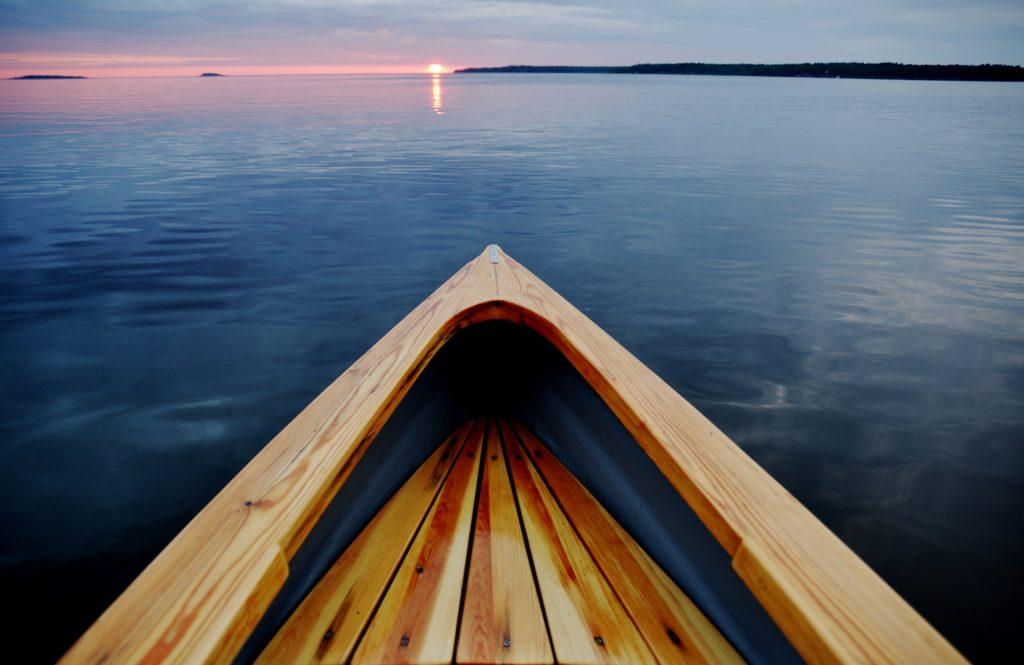 Kokkolan saaristo tarjoaa upeat maisemat melontaretken järjestämiseen. Illan tullessa aurinko luo viimeisiä valonsäteitään taivaanrannassa ja puinen kanootti tarjoaa kulkumahdollisuuden merellä omaan tahtiin. Tyyni ilta on mitä kaunein melontaretkelle. Kuvaaja Miia Parviainen.