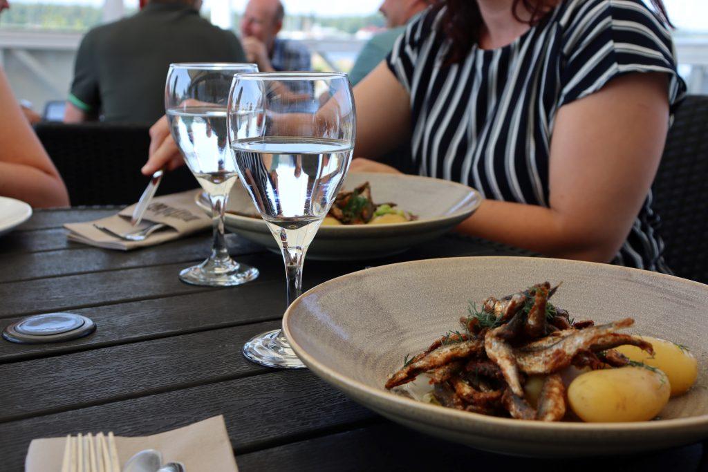 Kesäravintola Mustakarissa voit nauttia á la Carte annoksia merellisessä miljöössä. Lautasella on paistettuja muikkuja ja keitettyjä perunoita.