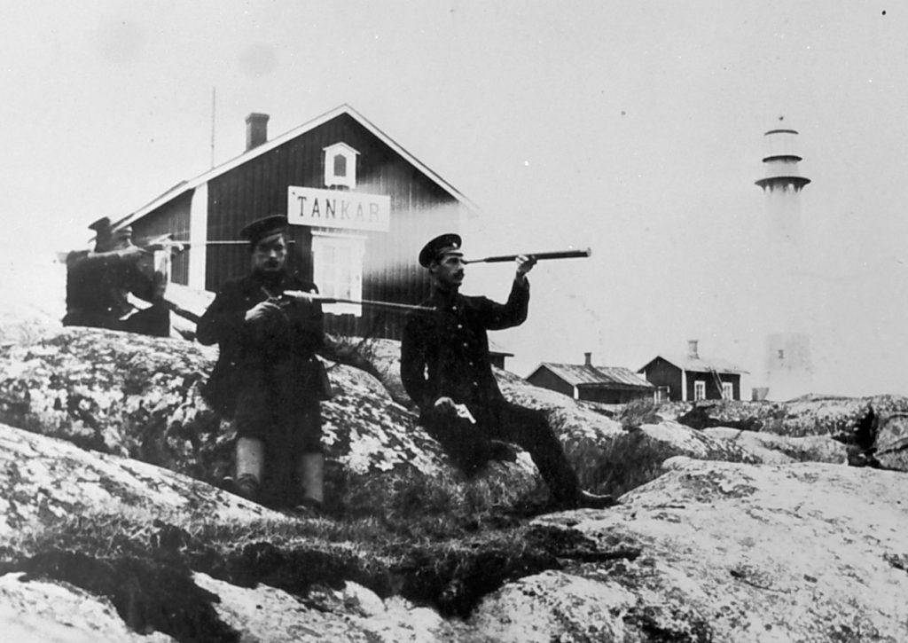 Vanha mustavalkokuva Tankarin majakkasaaresta. Kaksi miestä tarkkailee kivääreiden kanssa merelle ja yksi mies tarkkailee kaukoputkella. Kuva: K.H. Renlundin museo