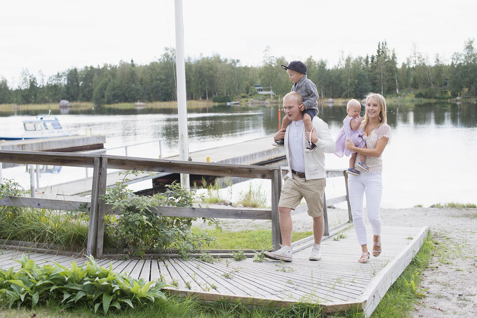4 henkinen perhe kävelemässä Köpmanholmenin laituria pitkin auringon paisteessa. PIenet lapset ovat vanhempien sylissä, toinen heistä olkapäiden päällä istumassa.