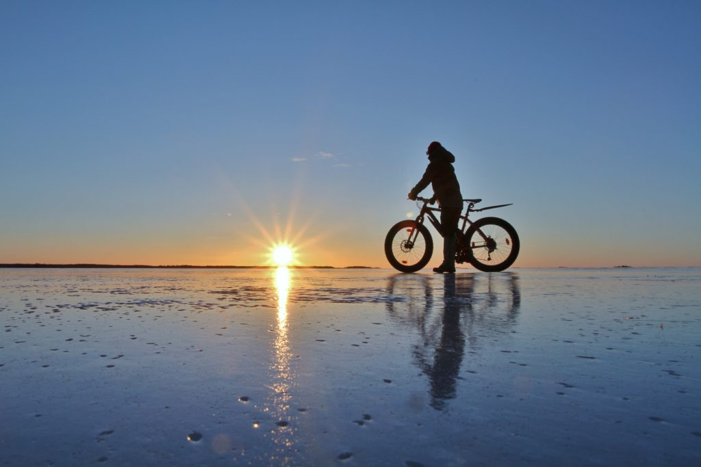 Talvinen ilma on houkuttanut pyöräilijän jäälle. Aurinko paistaa horistontissa, ja luo viimeisiä valonsäteitään pyöräilijään. Kuvaaja Miia Parviainen.