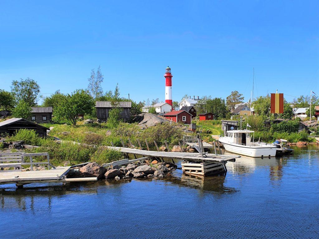 Tankarin majakkasaari kauniina kesäpäivänä. Punavalkea majakka hallitsee kokonaisuutta punaisten ja valkoisten mökkien lomasta. Rannassa on vene.