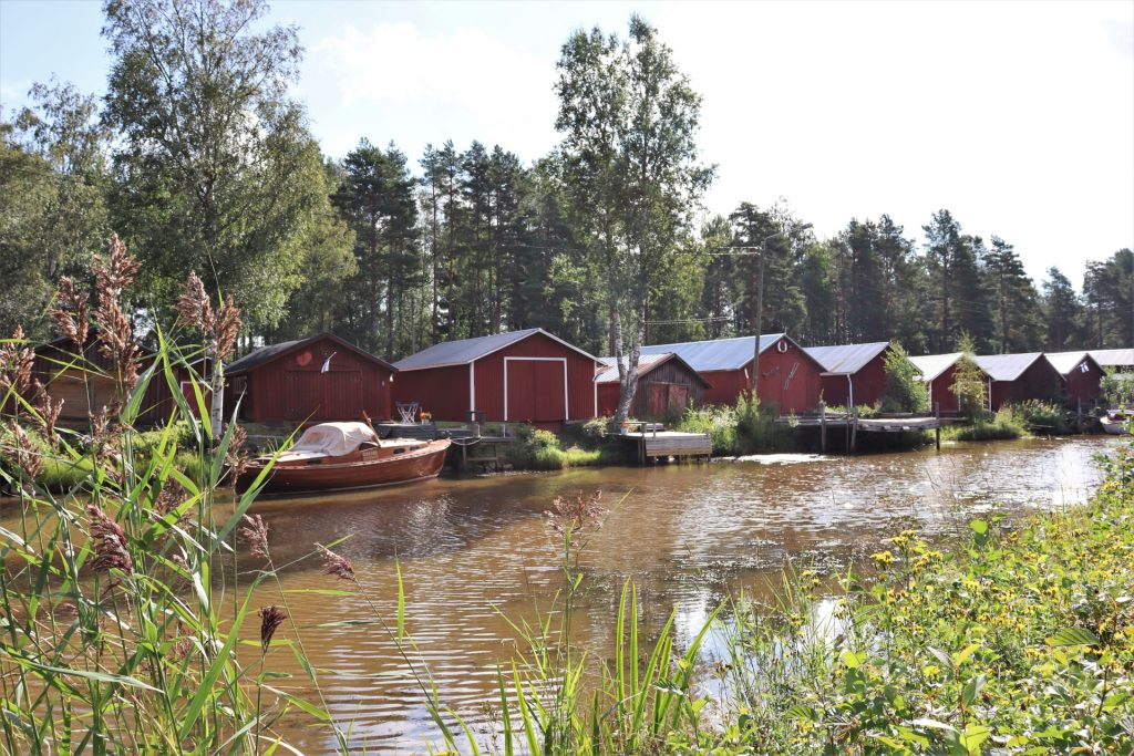 Ihastuttavat punaiset venevajat tuovat tunnelmaa kaupunginsalmi Suntin varrella. Puinen vene on parkkeerattu venevajan eteen kesäisenä päivänä, rantaheinikkojen kehystäessä vajoja.