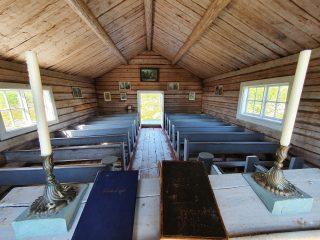 Tankarin kirkko sisältä. Seinillä on uskonnollisia tauluja ja kirkossa on vaaleansiniset kirkonpenkit.
