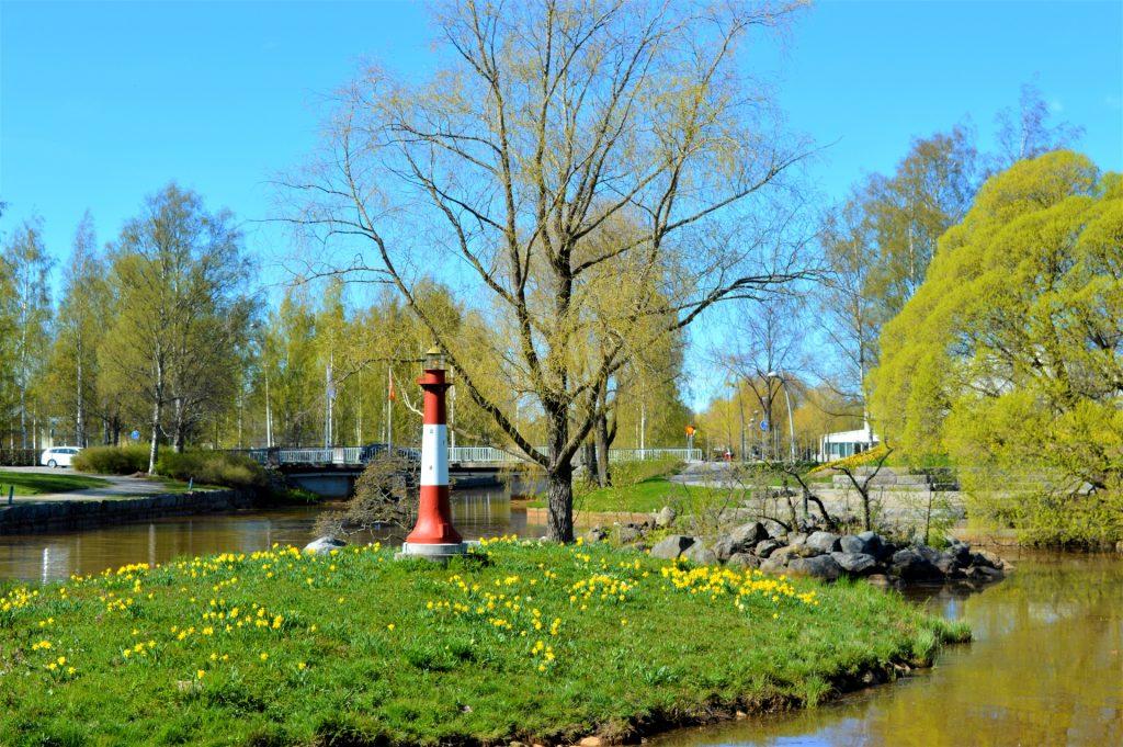 Kesä on tullut Kokkolaan ja kaupunginsalmi Suntissa sijaitsevassa Eskonsaaressa pienen koristemajakan ympärillä kukkivat voikukat. Lehdet ovat puhkeamassa puihin ja Sunti ympäröi pientä saarta.
