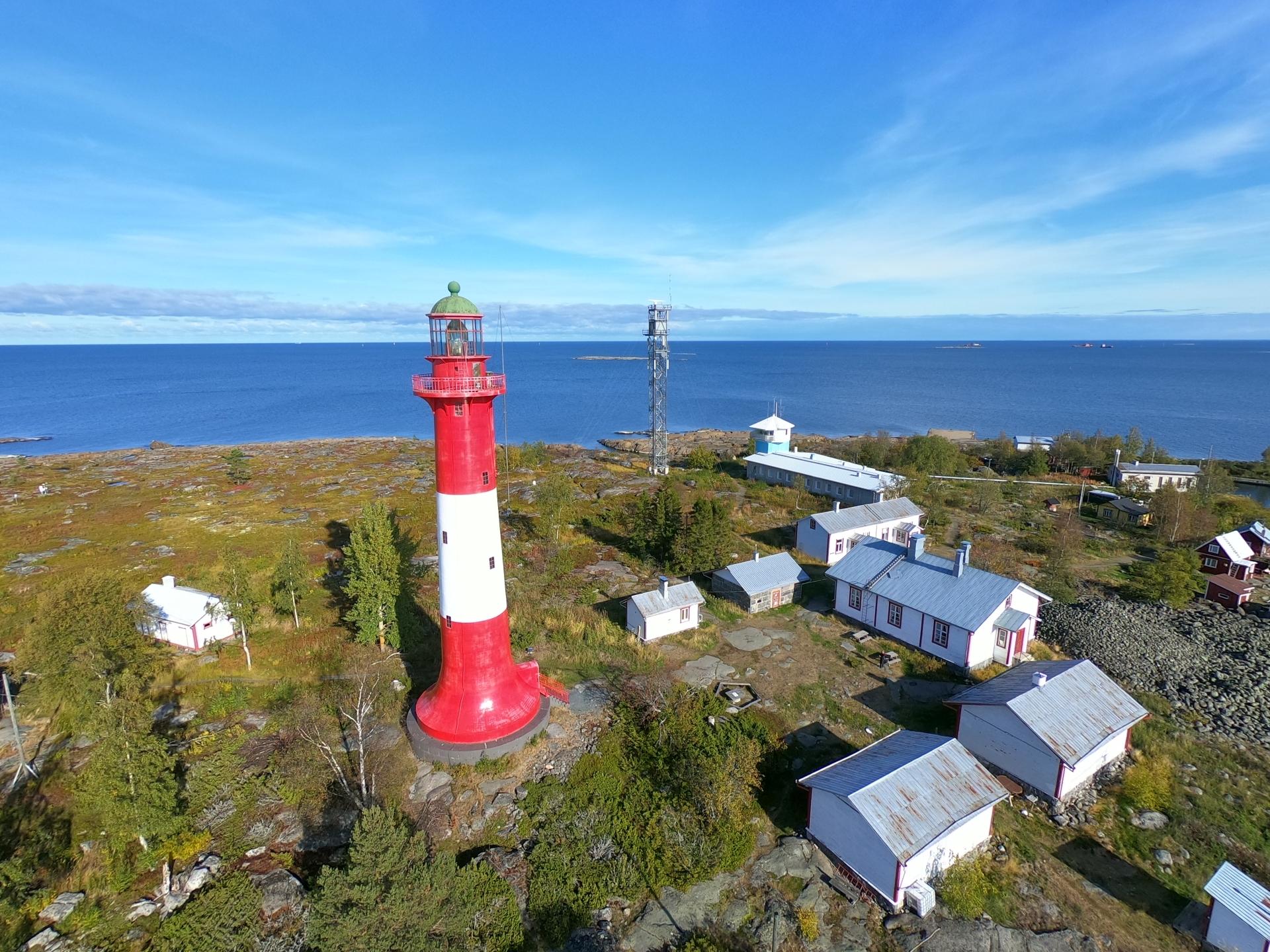 Tankarin majakkasaaren ilmakuvassa on vihreää luontoa ja valkoisia rakennuksia. Puna-valkea majakka hallitsee kokonaisuutta ja taustalla näkyy myös luotsiasema.
