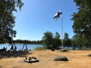 Köpmanholmenin ranta, jonka yhteydessä pieni leikki puisto. Suomen lippu liehuu salossa.