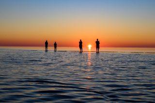 Kaunis kesäilta on saanut perheen ihastelemaan auringonlaskua Vattajan hiekkarannalle. Aurinko laskee horisontissa ja värjää taivaan syvän punaisen väreillä. Kuvaaja Hannu Tikkanen.