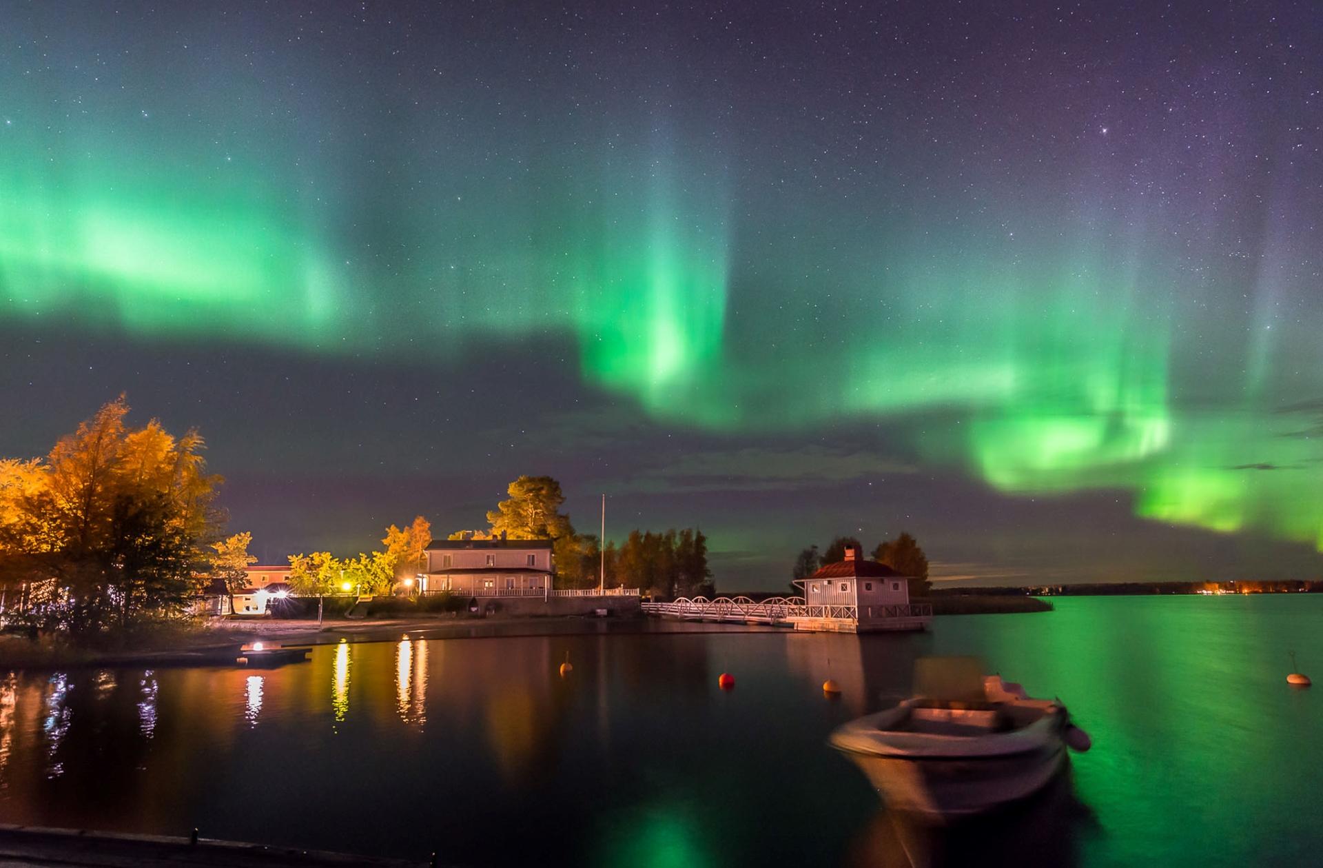 Kokkolan Villa Elba öisen revontulitaivaan alla. Kauniit vihreät revontulet, Aurora Borealis, valaisee meren vihreänä. Valot loistavat Nuorisokeskus Villa Elban pihassa ja merellä on yksi vene. Kuvaaja Hannu Moilanen.