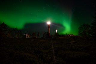 Upeat vihreät revontulet loimuavat Tankarin yllä tähtitaivaalla. Tankarin puna-valkoisen majakan valo loistaa yössä kirkkaana. Kuvaaja Hannu Tikkanen.