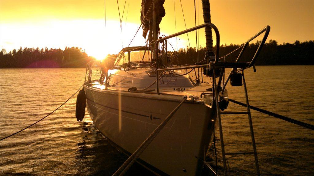 Tankarissa on viranomaislaiturin ja mökkiläisten venepaikkojen lisäksi suosittu vierasvenesatama. Vene kelluu satamassa auringon laskiessa.