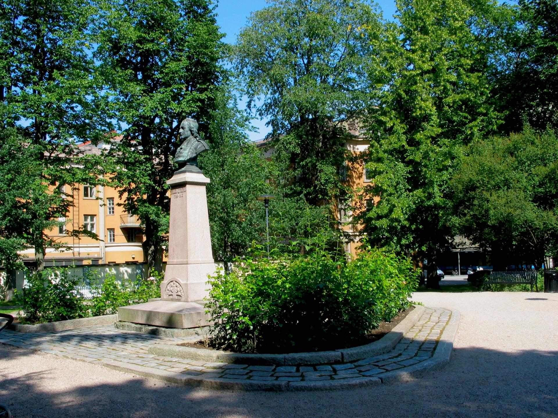 Chydeniuksen puisto kesäisenä päivänä. Anders Chydeniuksen patsaaseen loistaa aurinko.