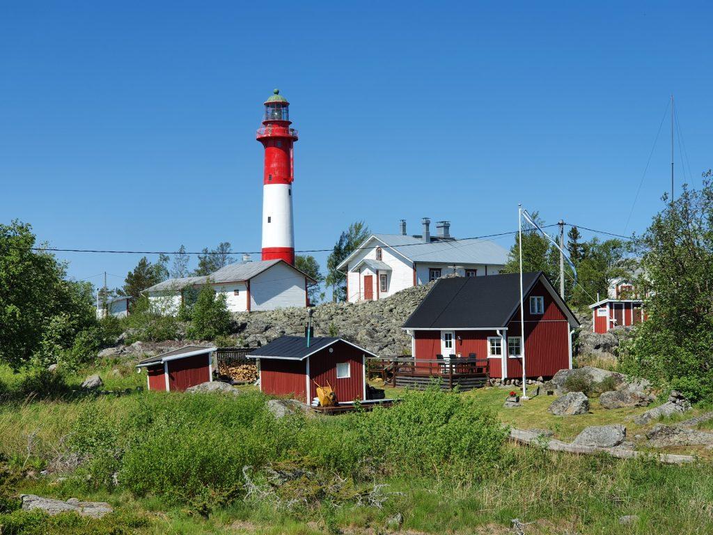 Tankarin majakkasaari kauniina kesäpäivänä. Punavalkea majakka hallitsee kokonaisuutta punaisten mökkien lomasta.