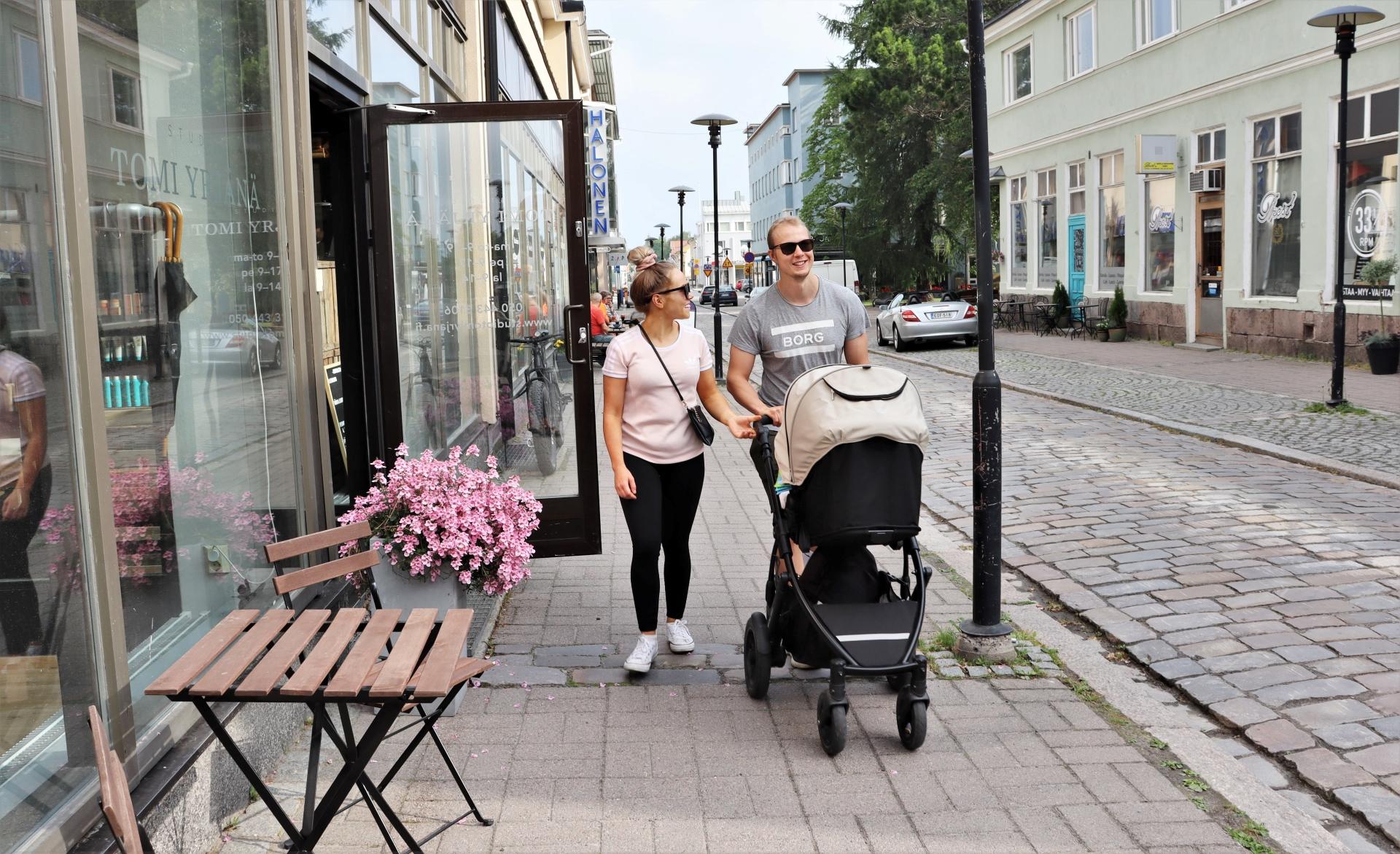 Perhe viettää kesäistä päiväänsä kävellen Kokkolan keskustassa mukulakivikadulla. Kivijalkaliikkeet ovat auki ja kaupan edessä on kukkia.