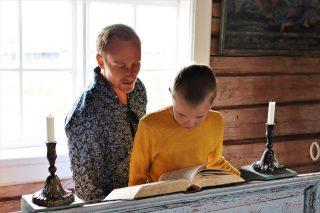 Isä ja poika lukemassa raamattua Tankarin kirkossa.