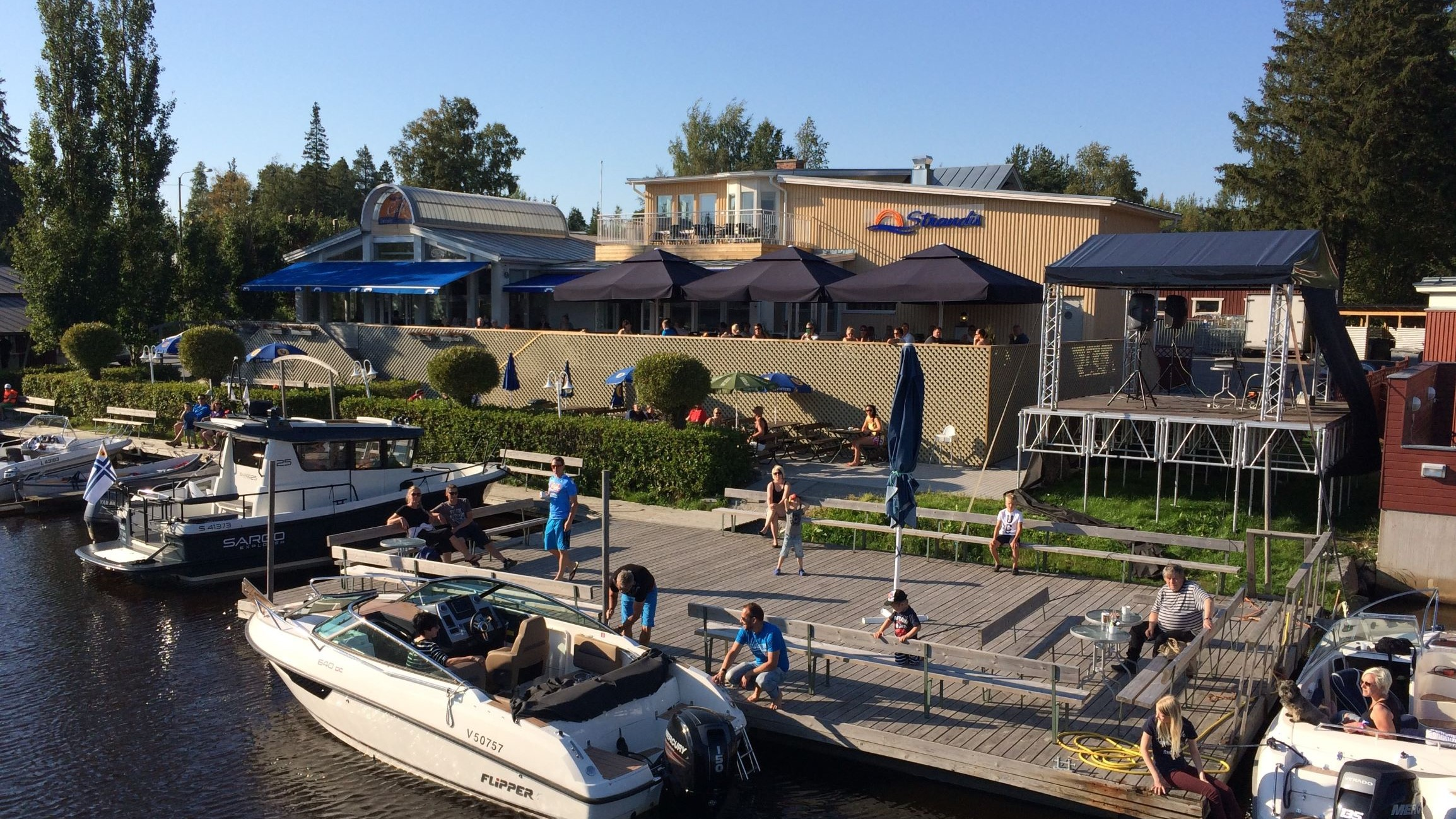 A bunch of people are sitting on the terrace and dock of Strandis on a summer day