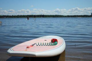 SUP-lauta kesäisellä rannalla, taustalla suppailijoita